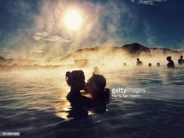 couple kissing while swimming in hot spring - blue lagoon iceland stock pictures, royalty-free photos & images