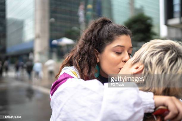 couple kissing while walking in the street - kiss stock pictures, royalty-free photos & images
