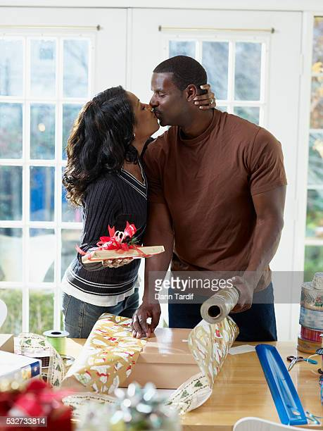 couple kissing while wrapping presents - african american christmas images stock pictures, royalty-free photos & images