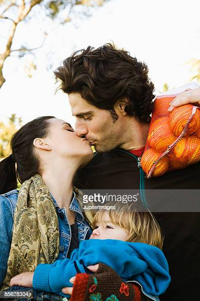 Couple kissing with son and bag of oranges