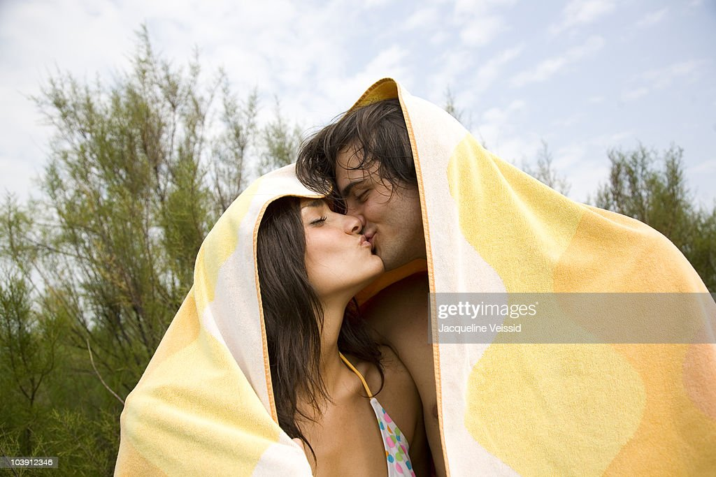 Couple kissing wrapped in beach towel : Stock-Foto