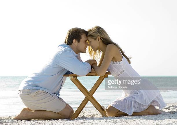 Couple kneeling on beach, nose to nose