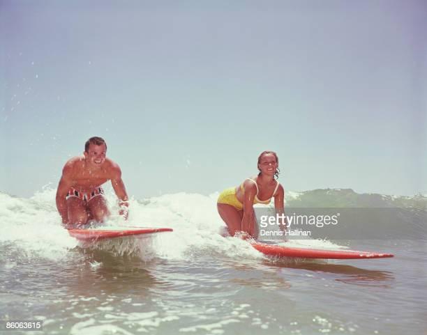 Couple Kneeling on Surf Boards Riding Ocean Surf