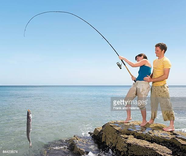 Couple landing a big fish off rocks