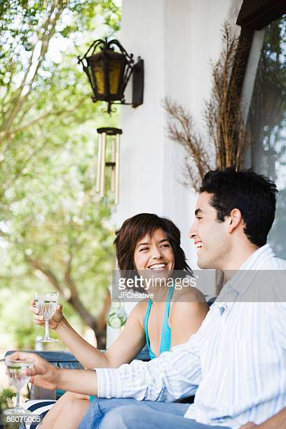 Couple laughing and drinking cocktails