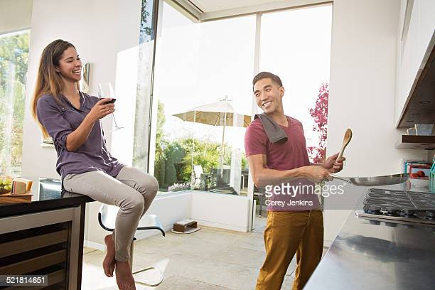 Couple laughing and fooling around whilst cooking in kitchen
