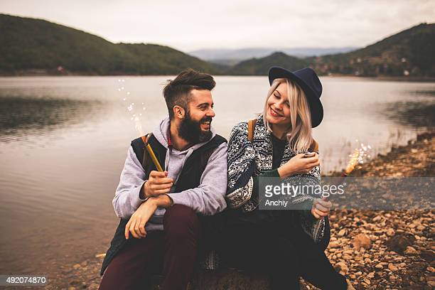 Couple laughing and holding Christmas sparklers.