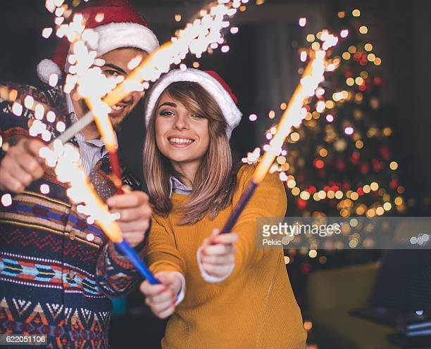 Couple laughing and holding Christmas sparklers