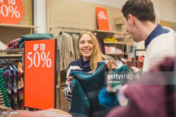 couple laughing and shopping in store - sale stock photos and pictures