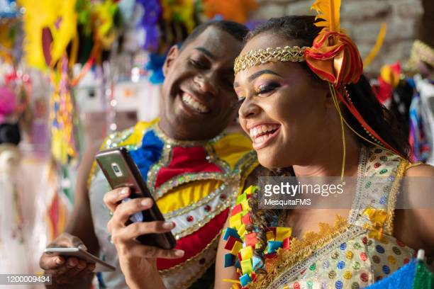 couple laughing and using mobile at carnival - frevo imagens e fotografias de stock