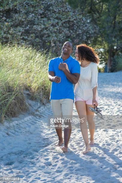 couple laughing and walking on beach - delray beach stock pictures, royalty-free photos & images