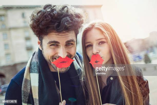 couple laughing at camera and holding large red lips - big lips stock photos and pictures