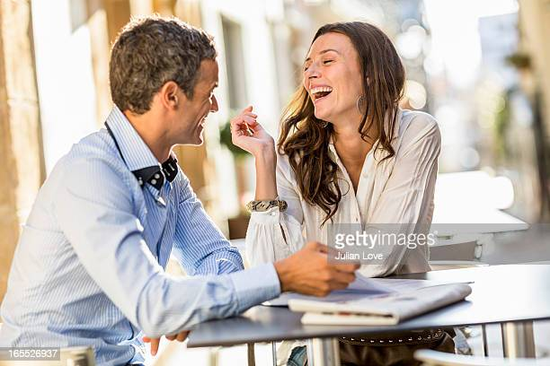 couple laughing at sidewalk cafe - オープンカフェ ストックフォトと画像