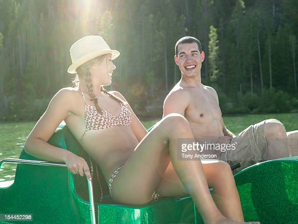 Couple laughing in paddle boat at mountain lake