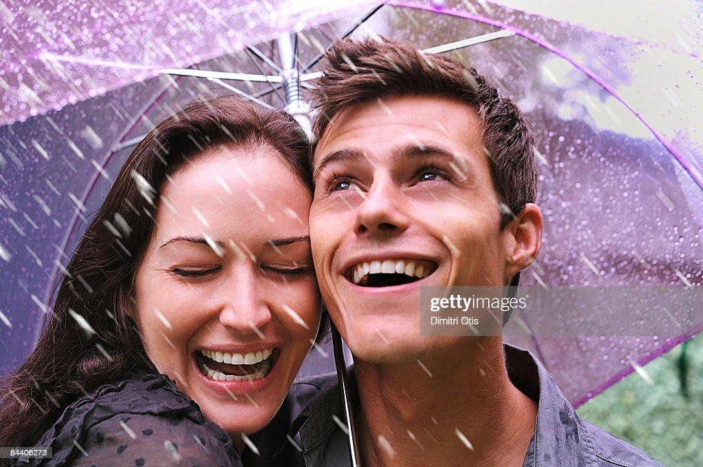 Couple laughing in rain under purple umbrella : Stock Photo