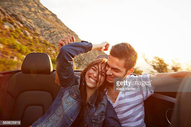 Couple laughing in the backeat of car