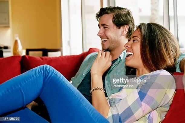Couple laughing on sofa