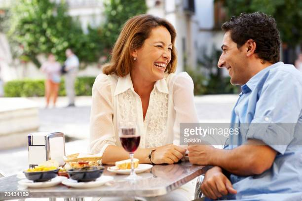 couple laughing over meal at outdoor restaurant - tapas stock photos and pictures