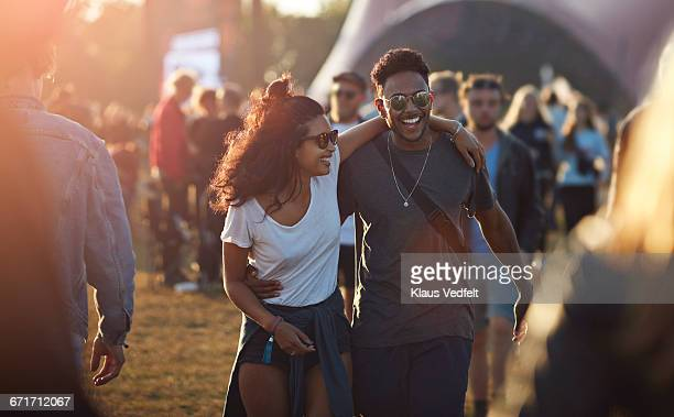 couple laughing together at big festival - music festival ストックフォトと画像