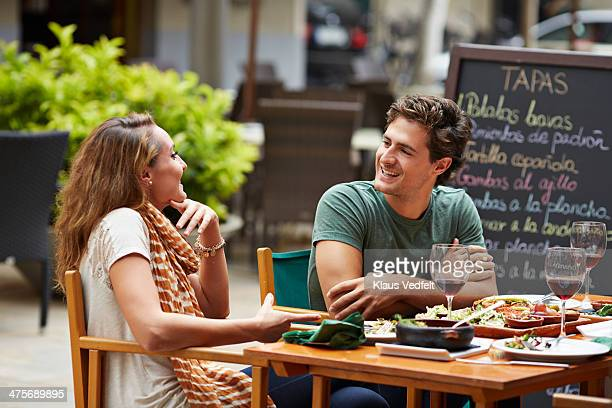 couple laughing together at restaurant - klaus vedfelt mallorca stock pictures, royalty-free photos & images