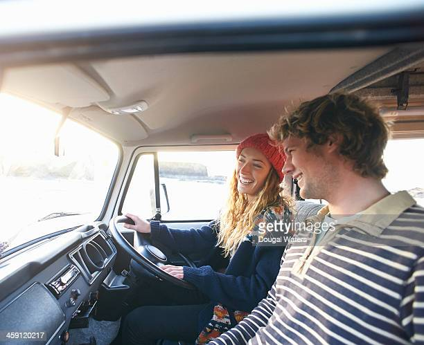 Couple laughing together in camper van.