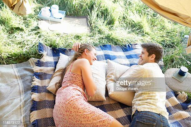 Couple laughing together in tent doorway.