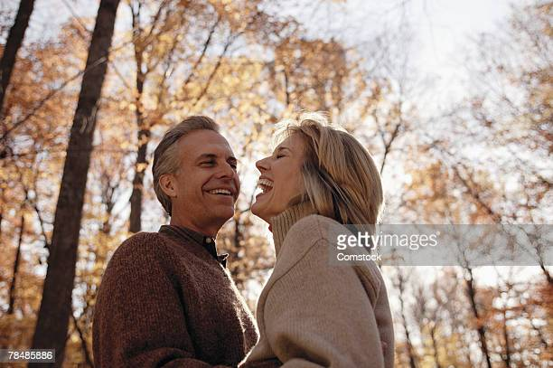 couple laughing together outdoors - 50 59 jaar stockfoto's en -beelden