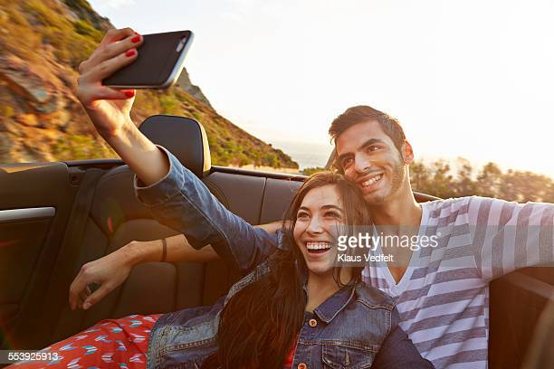 Couple laughing while making selfie in car