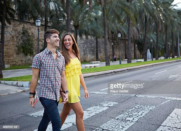 couple laughing while walking pedestrian crossing - casal heterossexual - fotografias e filmes do acervo