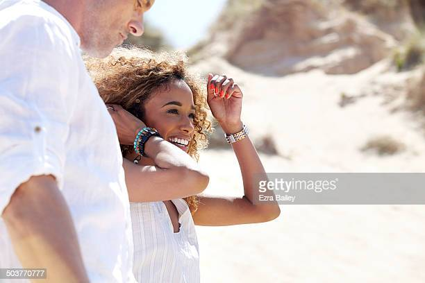 A couple laughing while walking through sand dunes