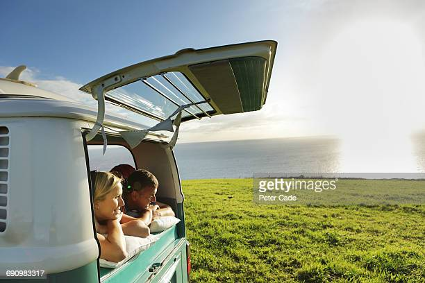 couple laying camper looking out the back at view - camper van stock pictures, royalty-free photos & images