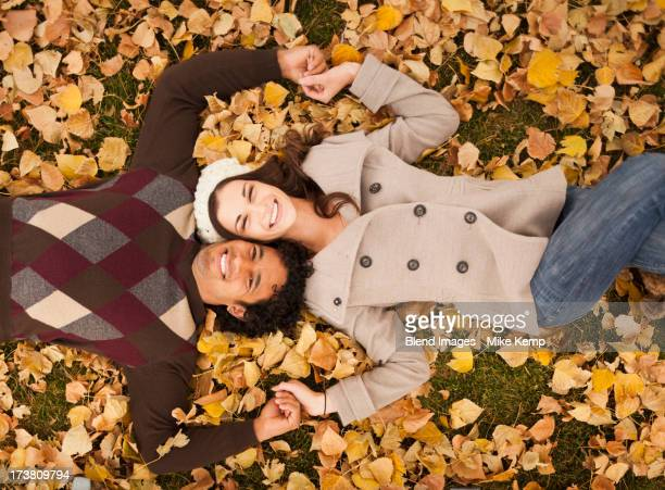 Couple laying in autumn leaves