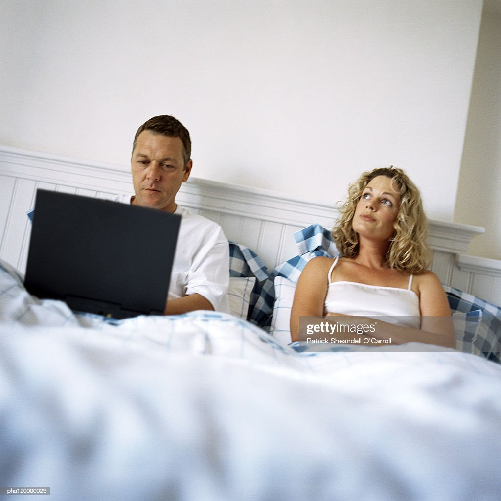 Couple laying in bed, man using laptop computer : Stockfoto