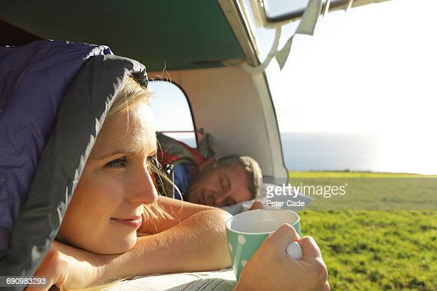 Couple laying in camper, woman looking at view