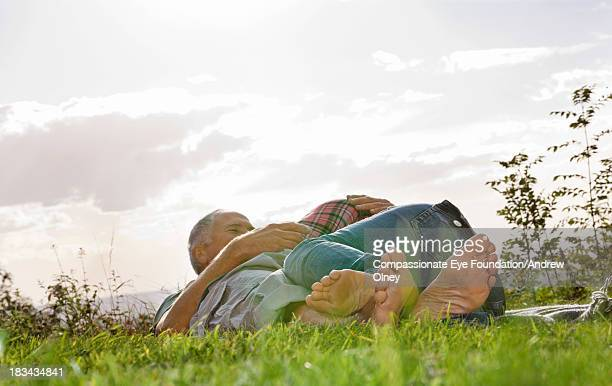 Couple laying in grass hugging