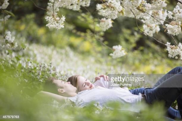 Couple profiter en herbe sous arbre avec fleurs blanches