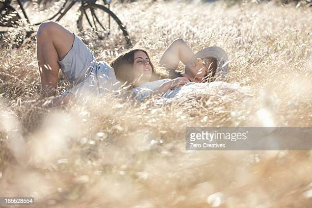 Couple laying in tall grass