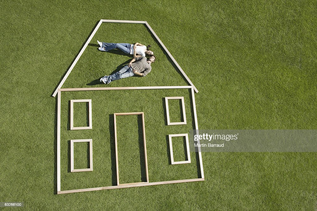 Couple laying inside house outline : Stock Photo