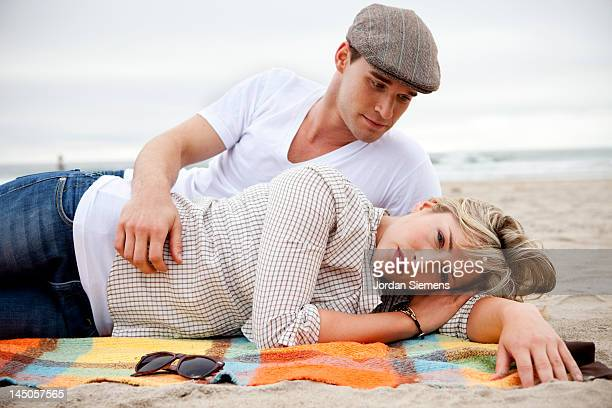 Couple laying on a blanket at the beach.