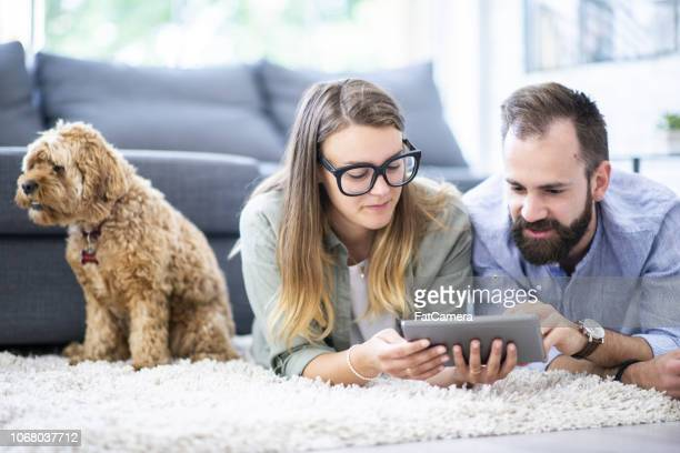 couple laying on a rug looking at a tablet - borrowing stock pictures, royalty-free photos & images
