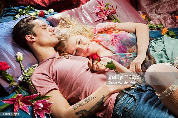 Couple laying on bed surrounded by flowers.