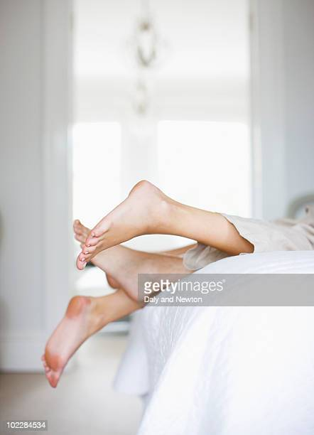 couple laying on bed together - couple lit photos et images de collection