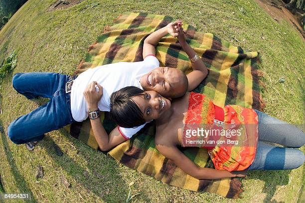 couple laying on each other's shoulders in a park. pietermaritzburg, kwazulu-natal province, south africa - pietermaritzburg stock pictures, royalty-free photos & images