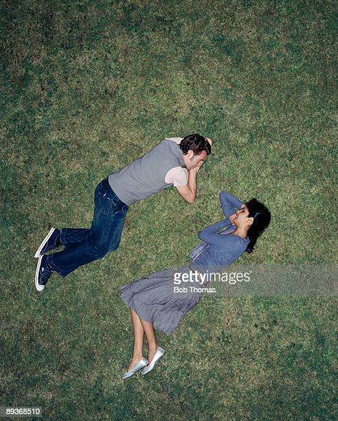 couple laying on grass - lying down stock pictures, royalty-free photos & images