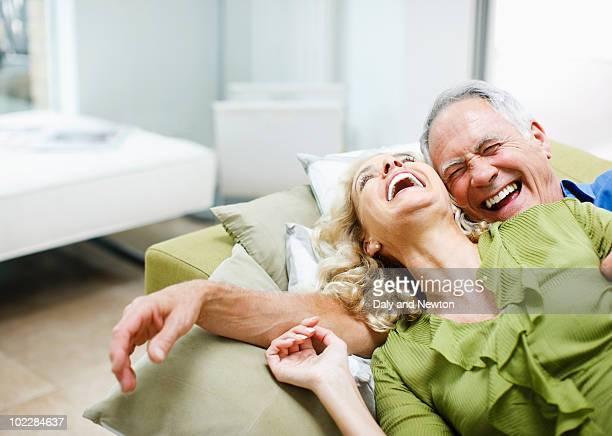 couple laying on sofa together - quinquagénaire photos et images de collection