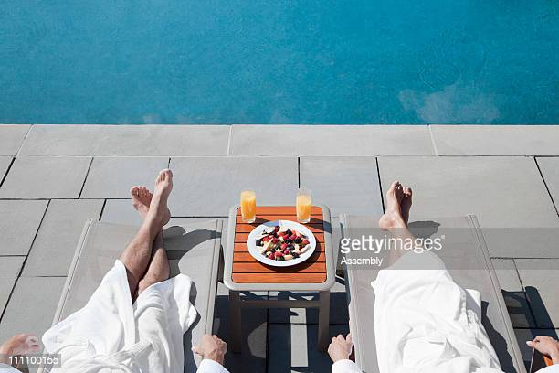 Couple laying poolside with food