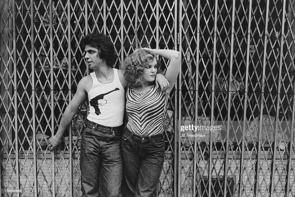 A couple lean against a shop shutter in Midtown Manhattan, New York City, 1979.