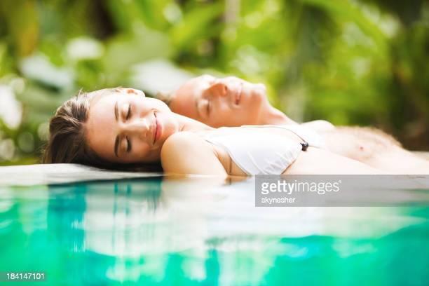 Paar leaned am Rande des tropischen pool