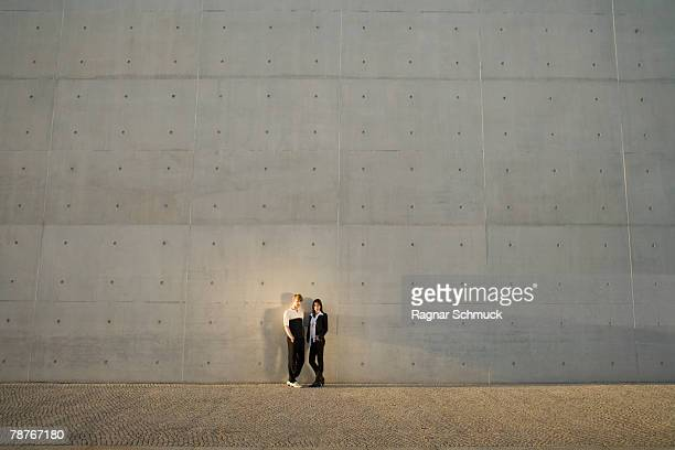 A couple leaning against a wall