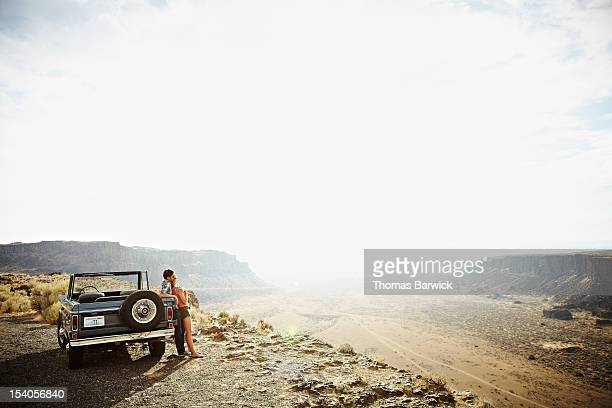 couple leaning against convertible on side of road - convertible stock pictures, royalty-free photos & images